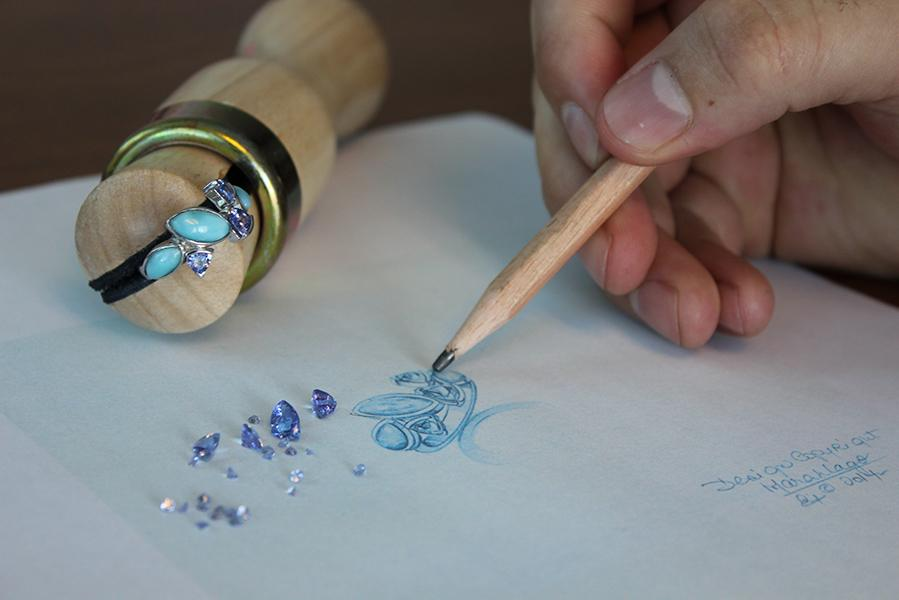 Marahlago designer hand drawing a jewelry piece. Blue spinel is scattered next to the drawing.